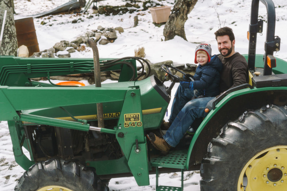 A father and small son drive a tractor.