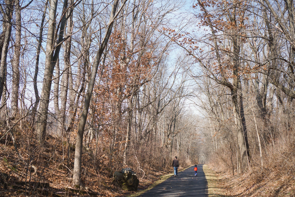 A father and daughter walk along the Rail Trail.