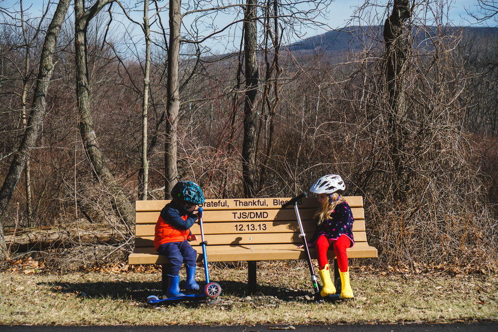 Two kids stop at rest on a bench on the Rail Trail.