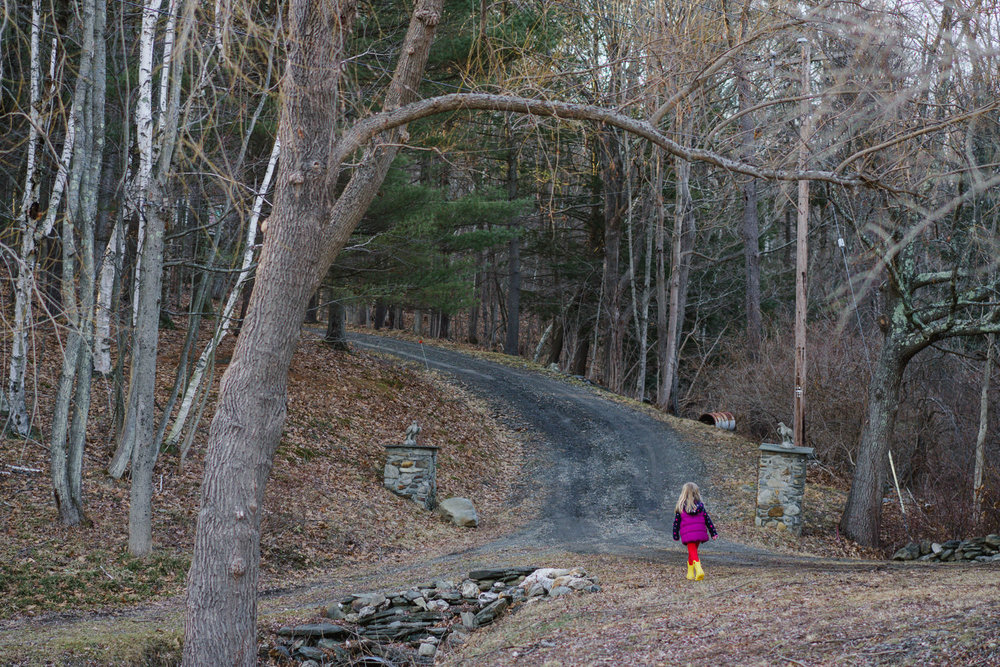 A little girl walks up a driveway in the woods.