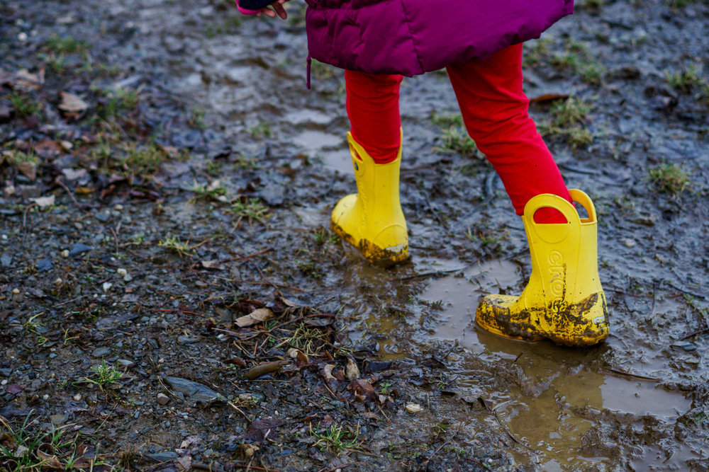 A little girl in yellow boots walks through the mud.