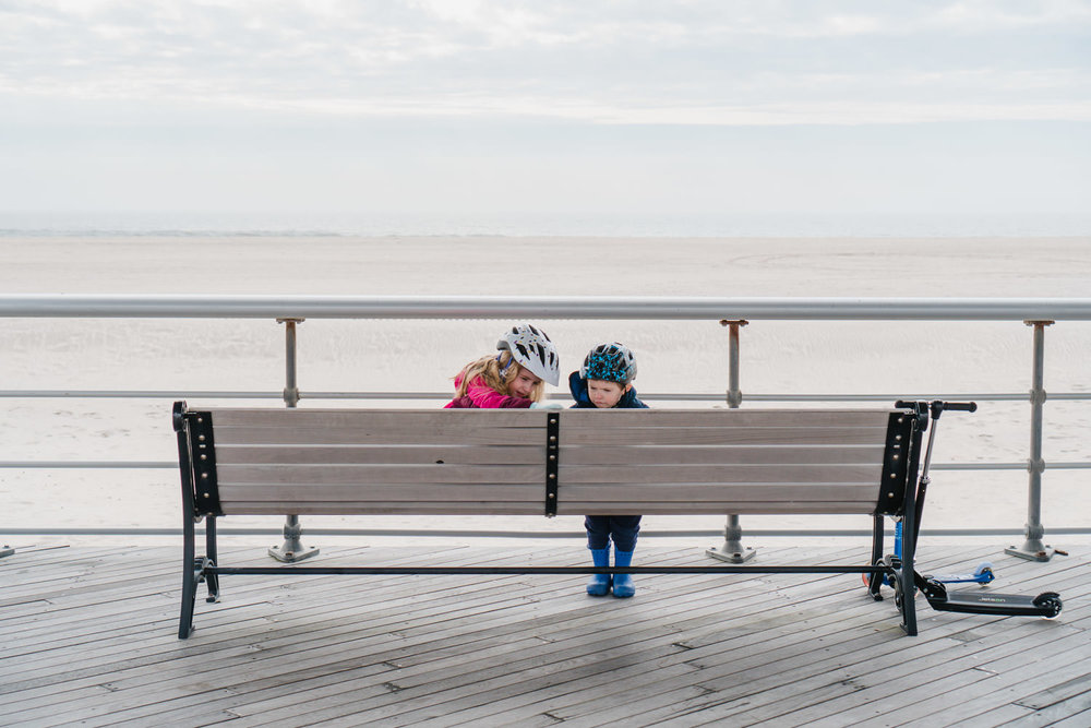 Two kids read an inscription on a bench at Jones Beach.