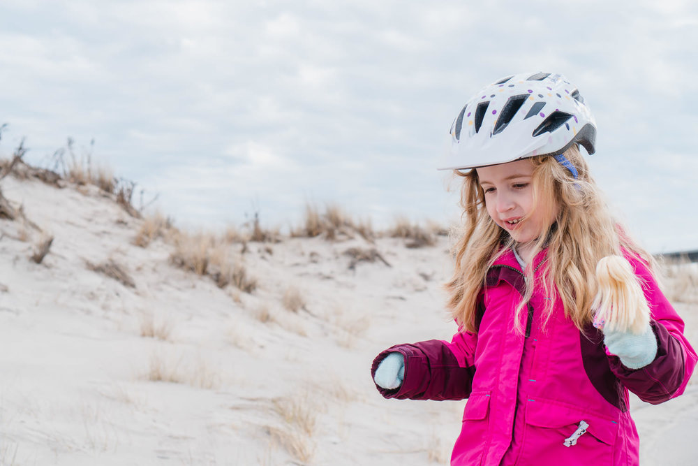 A little girl in a bike helmet stands near some sand dunes.