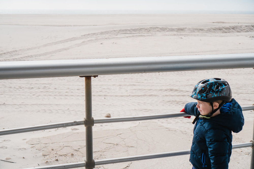 A little boy in a bike helmet looks out at the view at Jones Beach.