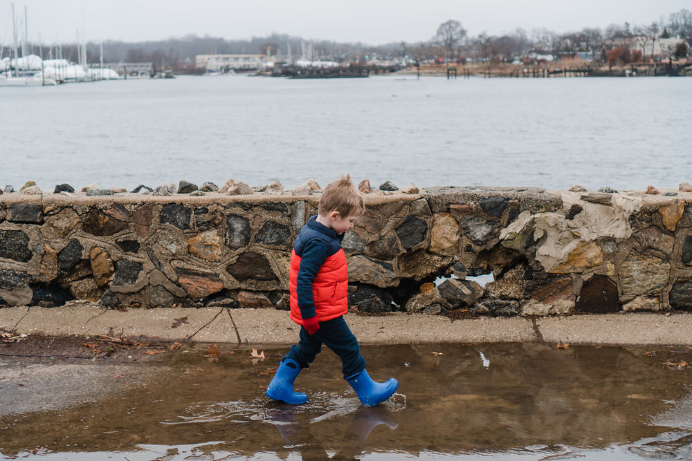 A little boy walks through a large puddle in Port Washington.