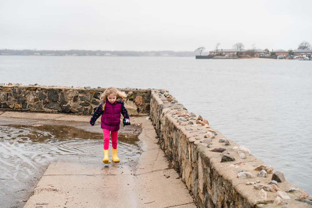 A little girl splashes in puddles in Port Washington.