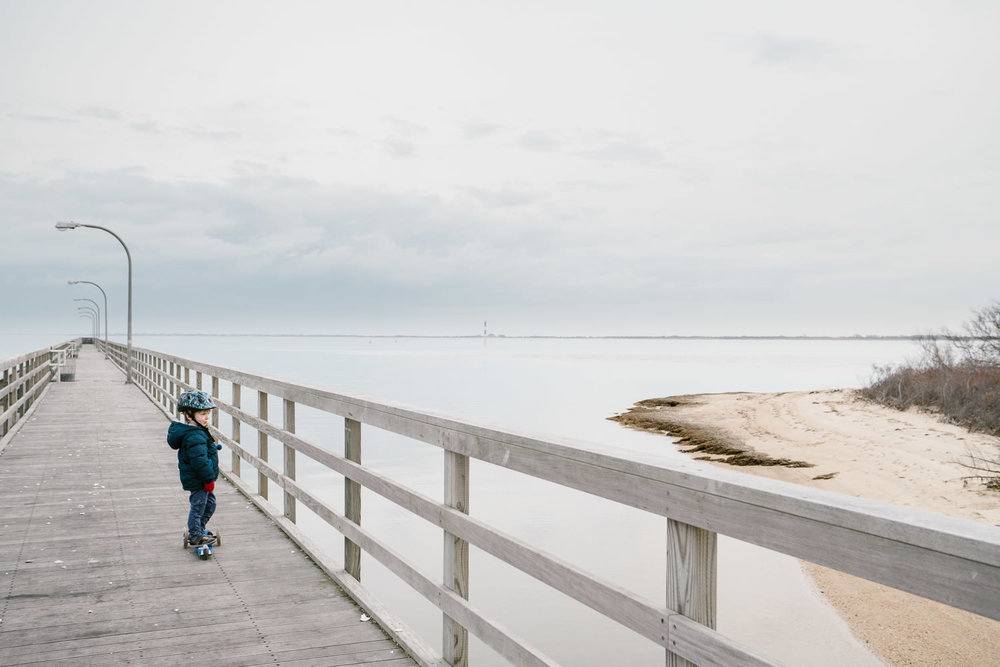 A little boy stands on the pier at Captree State Park.