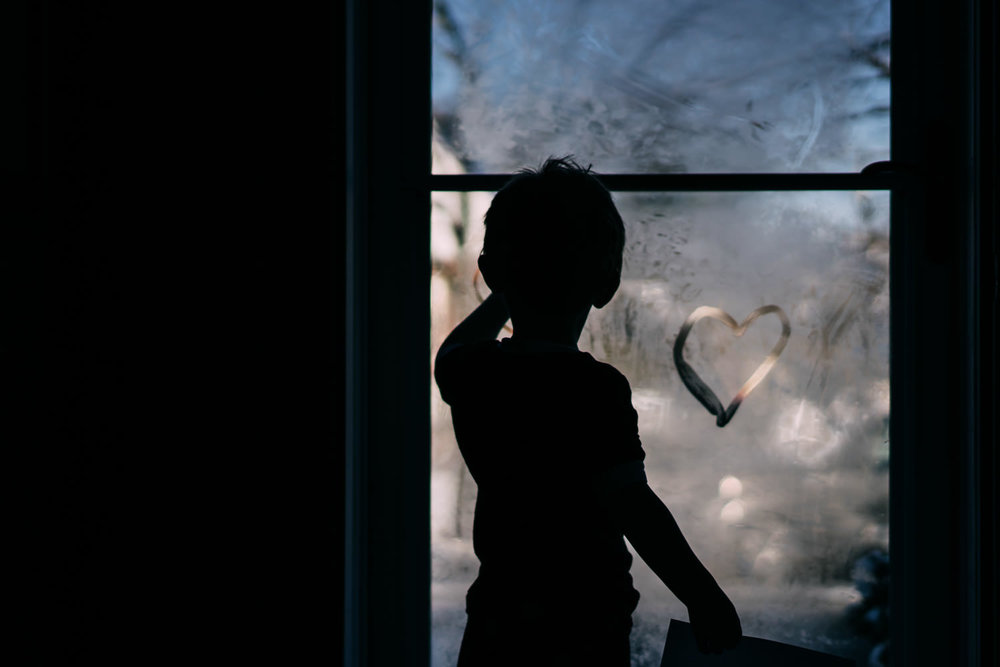 A little boy draws a heart with his finger onto a steamy window.