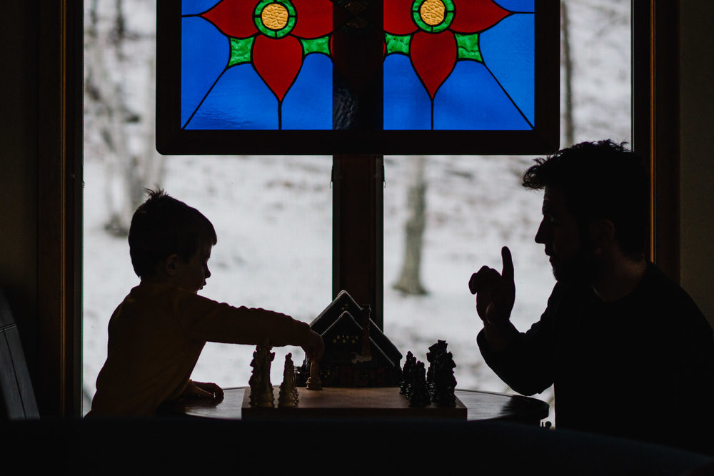 A father teaches his son to play chess.