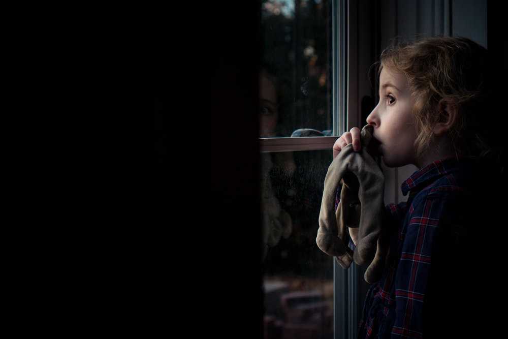 A little girl sucking her thumb looks out a glass storm door.