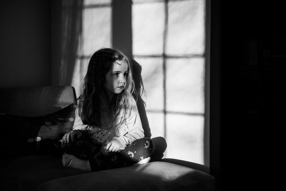 A little girl sits in a patch of sunshine coming through a window.