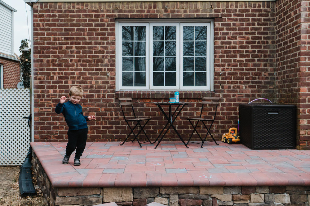 A little boy dances on his front porch.