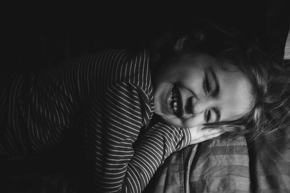A little girl lying down laughs.