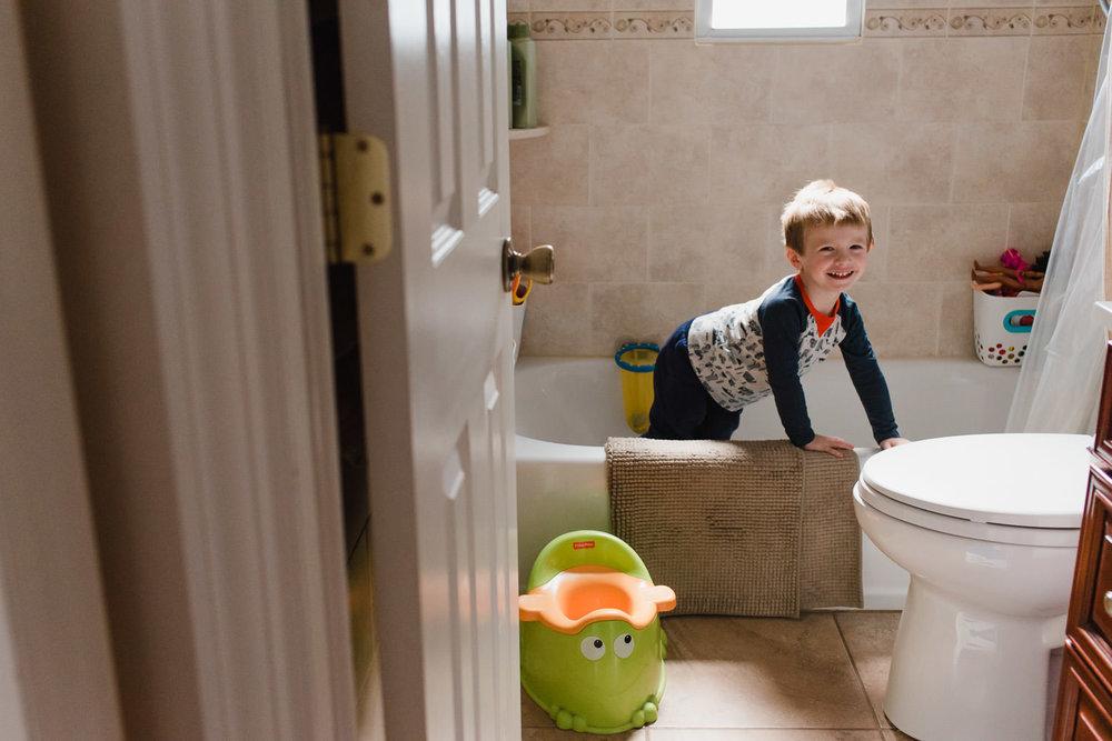 A little boy climbs into a tub.