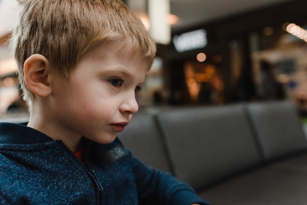 A little boy sits down at the mall.
