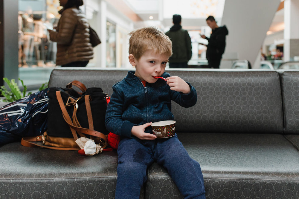 A little boy eats frozen yogurt at the mall.