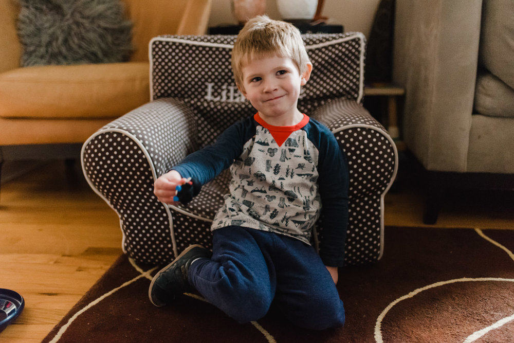 A little boy sits in a plush chair in a living room.