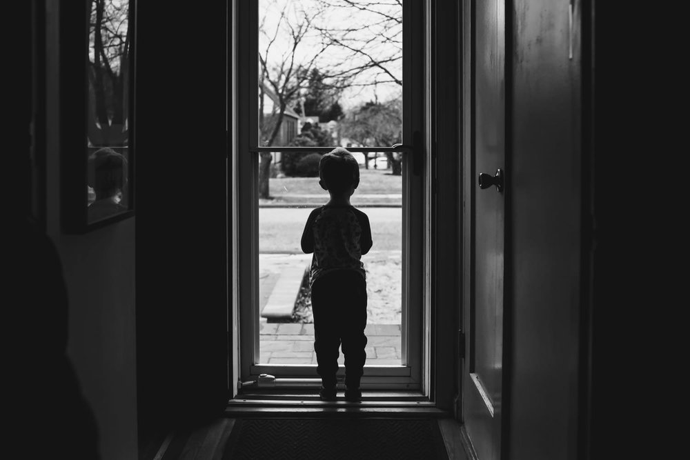 A little boy stands at the front door and looks out.