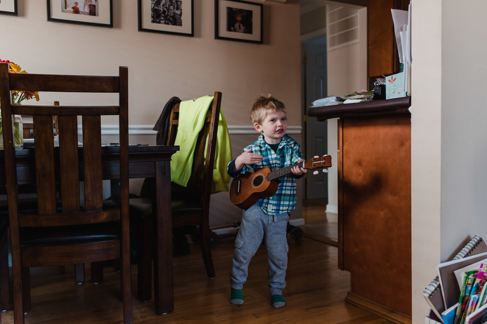 A little boy plays the ukulele in the dining room.