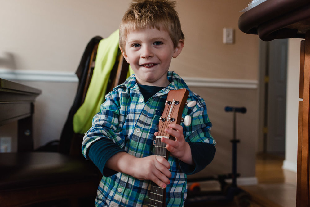 A little boy smiles while holding a ukulele.