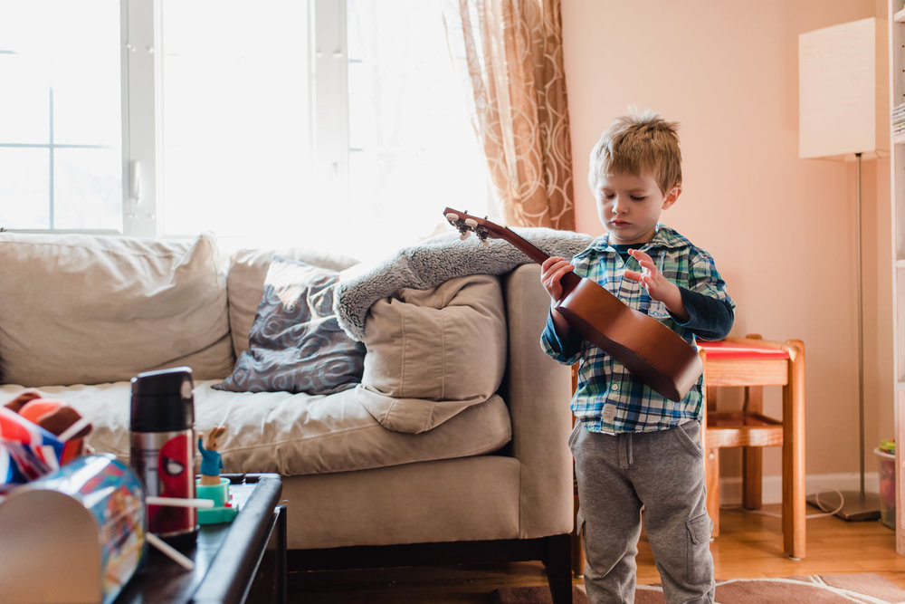 A little boy plays a ukulele in the living room.