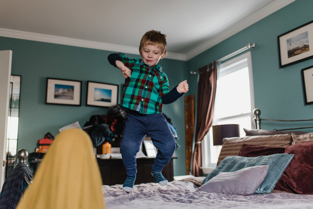 A little boy jumps on the bed.