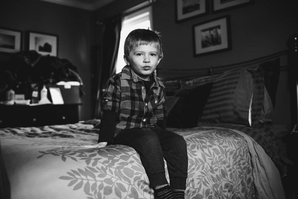 A little boy sits on the edge of his parents' bed.
