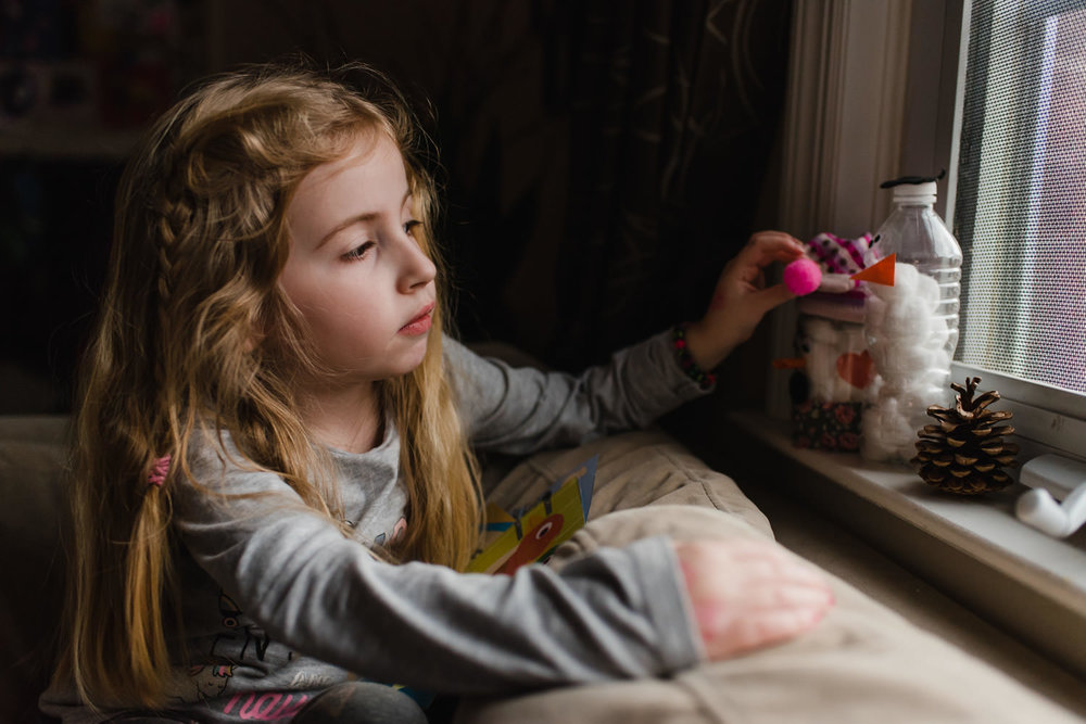 A little girl plays with some crafts on the windowsill.