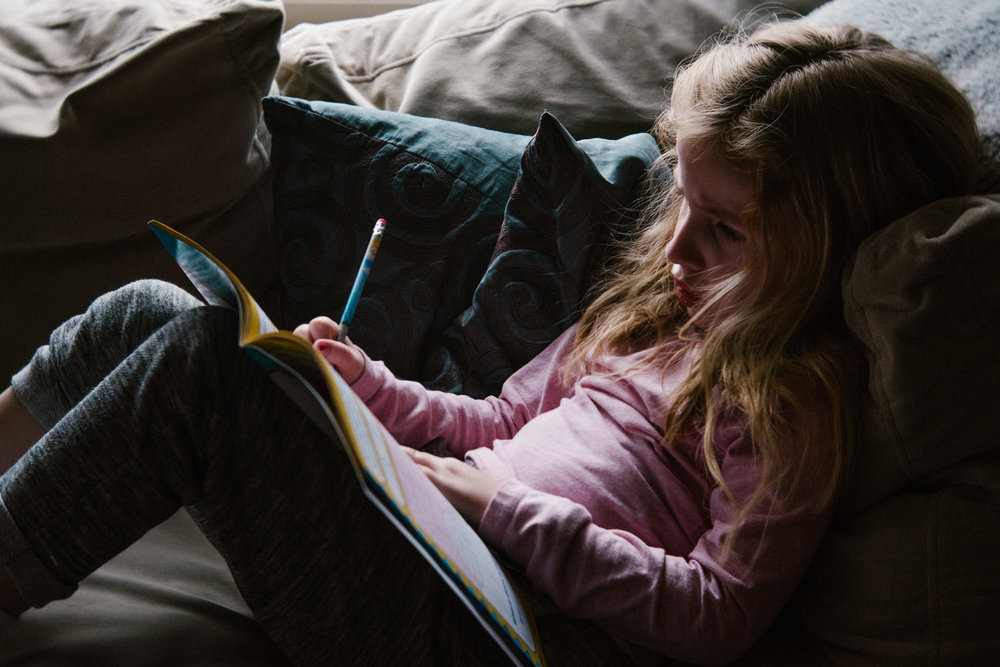 A little girl writes in a notepad while lying on the couch.