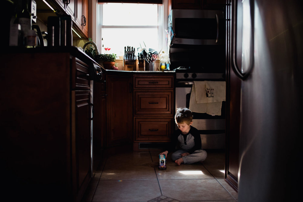 A little boy plays in a patch of light on the kitchen floor.
