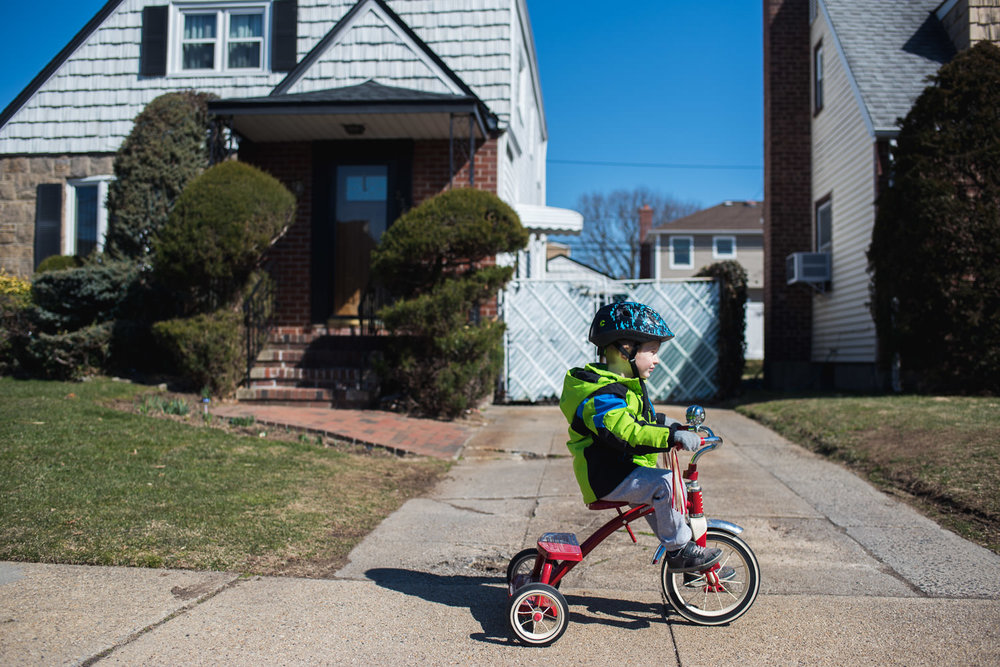 A little boy rides a tricycle along the sidewalk.