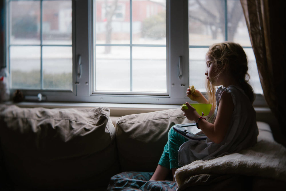 A little girl perches on the back of a couch and eats breakfast.