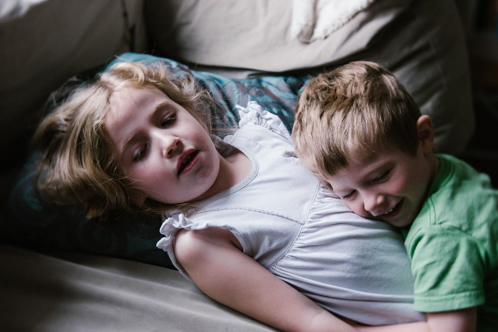 Two children embrace each other on the couch.