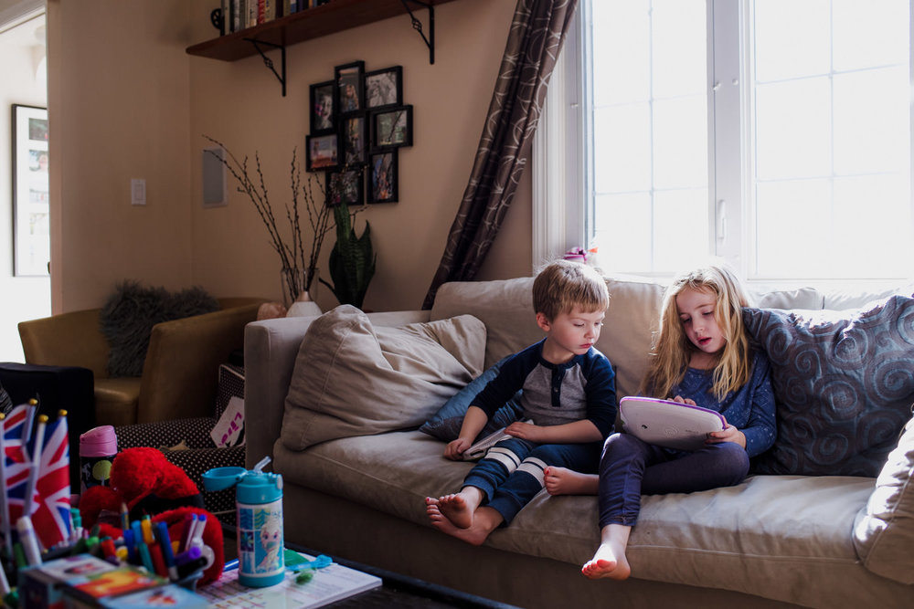 Two children play with a tablet on the couch.