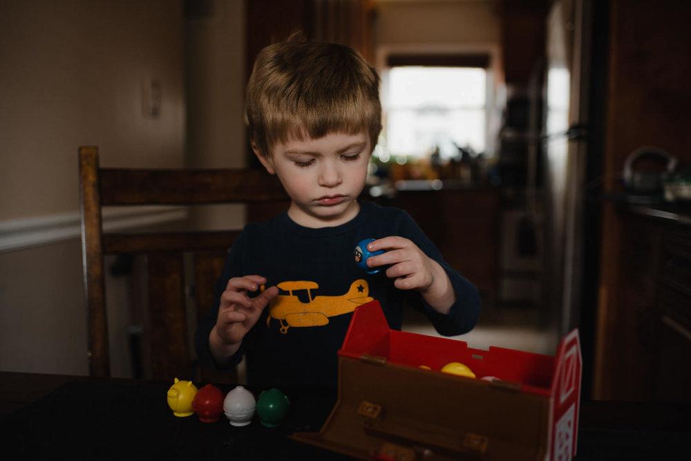 A little boy plays with a Yahtzee farm game.
