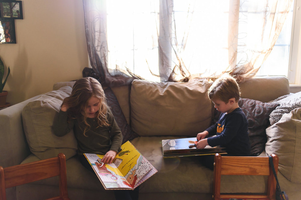 Two kids read books on the couch.