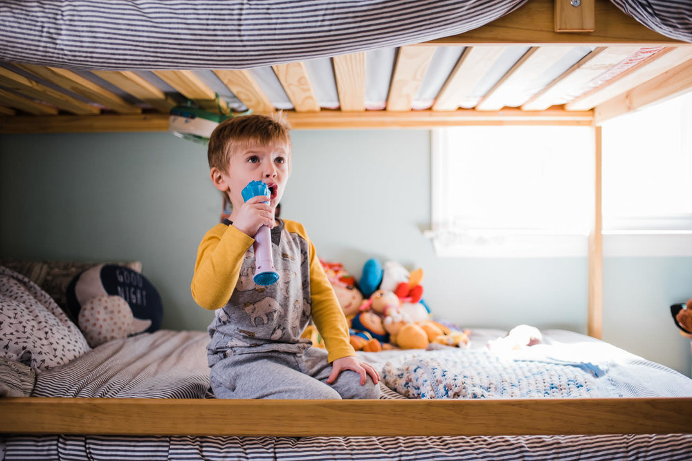 A little boy sings into a microphone in the bottom bunk of a bed.