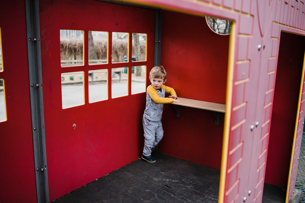 A little boy plays in a playhouse.