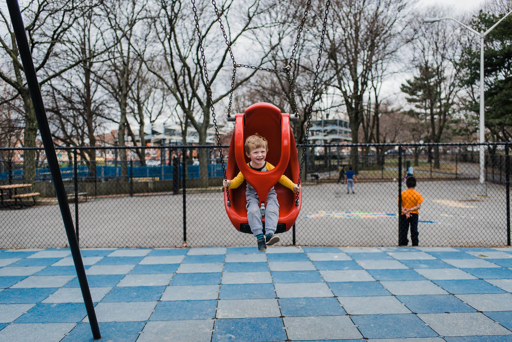 A little boy swings on a playground swing.