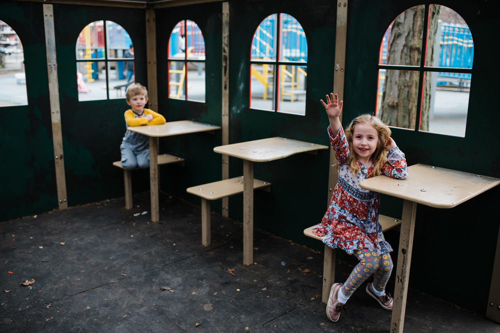 Two kids play in a schoolhouse structure at a playground.