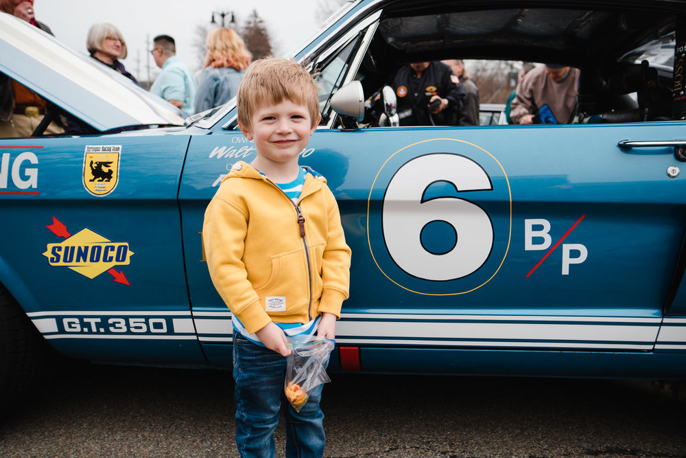 A little boy poses in front of a car at the Garden City car show.
