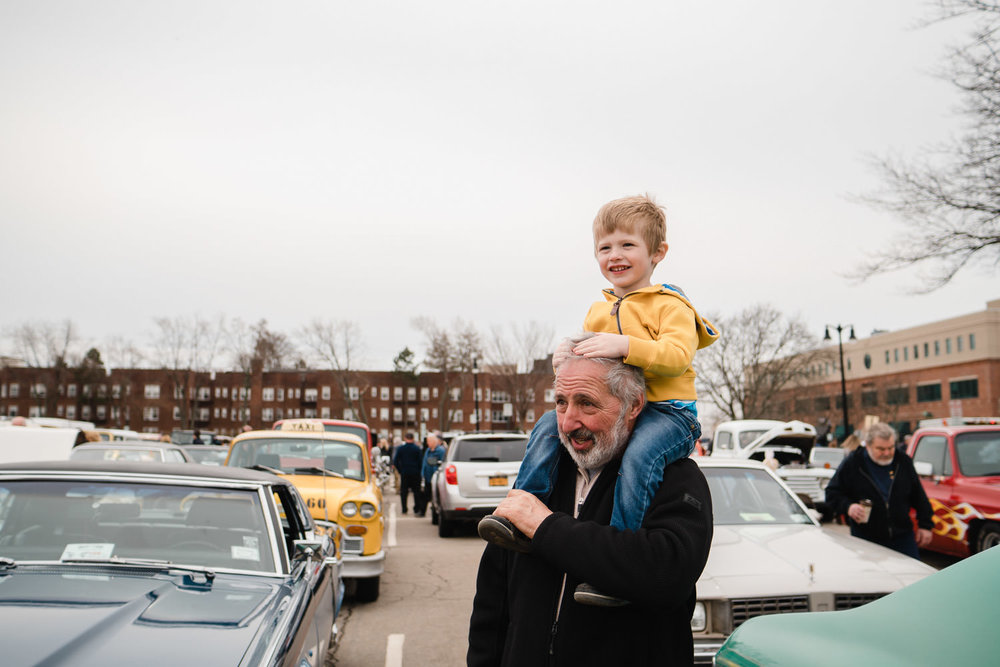 A little boy rides on his grandfather's shoulders.