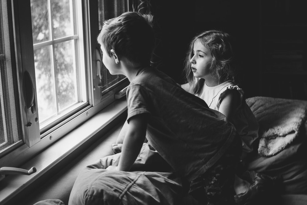 Two children look out a window.