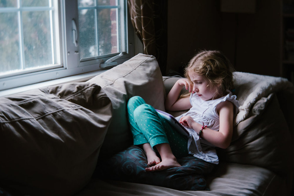 A little girl curls up on a couch and plays with a tablet.