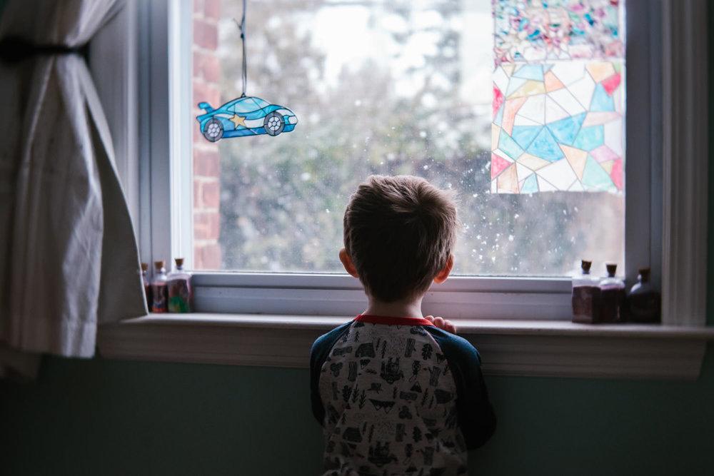 A little boy looks out a window.