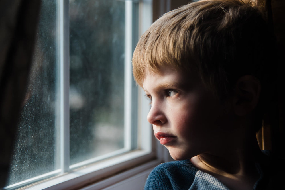 A portrait of a little boy looking out a window.