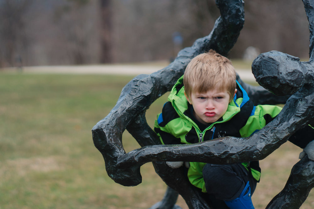 A little boy makes a funny face while climbing a sculpture at the Norman Rockwell Museum.