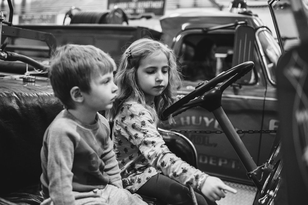 Two kids play in a fire truck at the fire museum in Hudson.