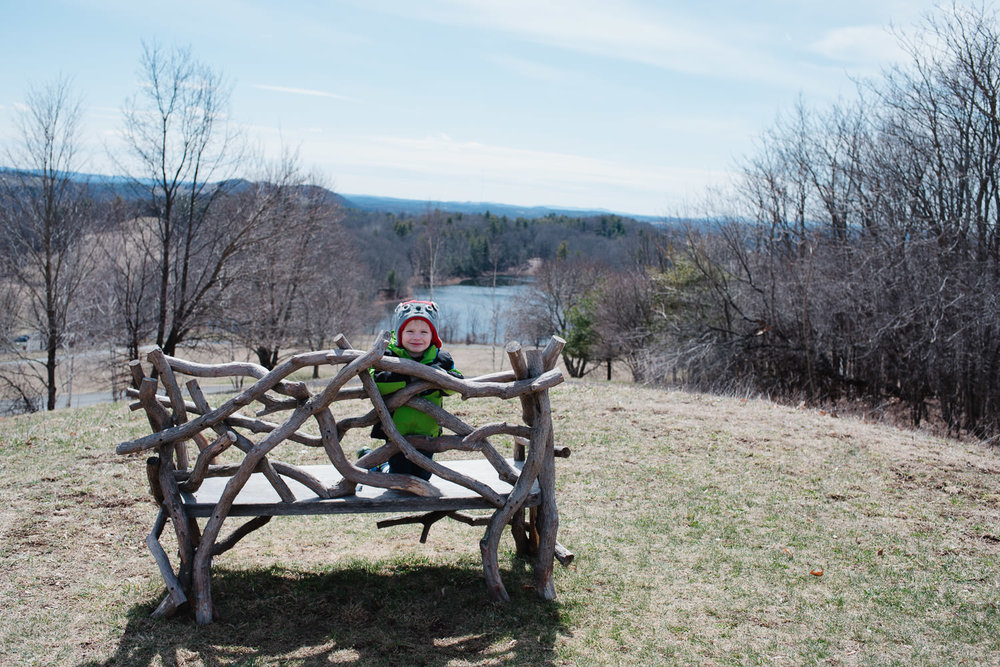 A little boy on a bench overlooking the Hudson River.