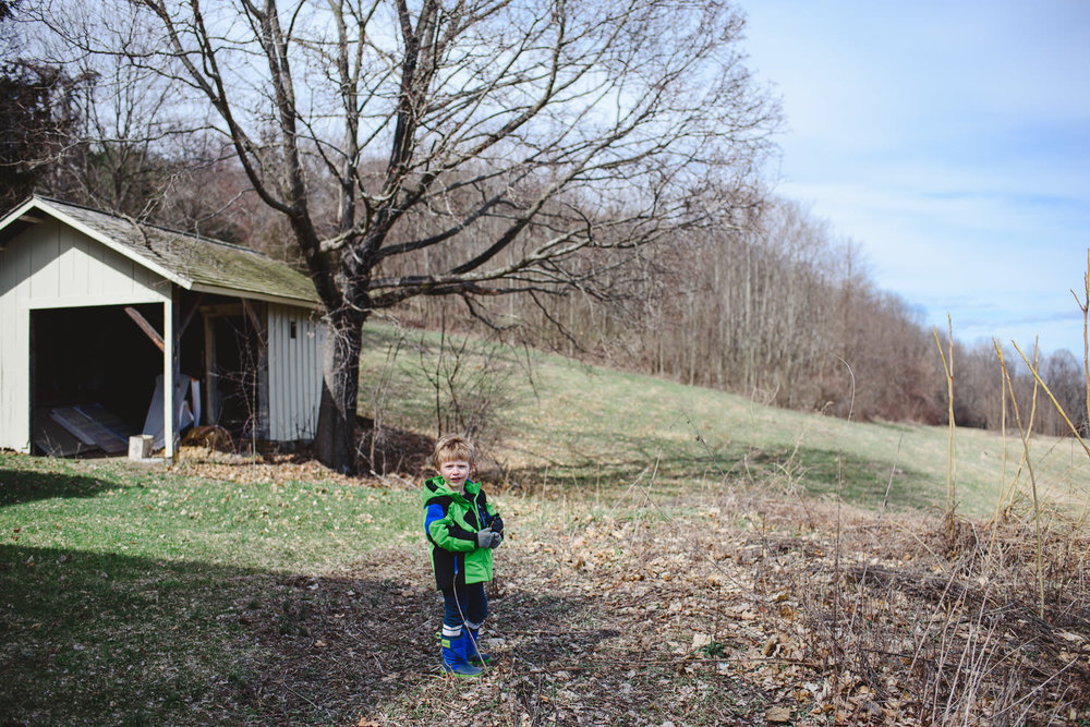 A little boy stands near the Cosy Cottage at Olana.